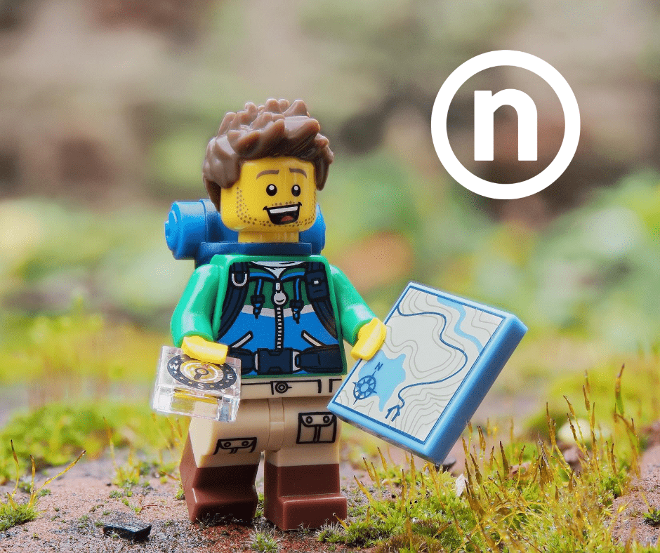 Lego Helped Associates Build Creativity and Relationships - image of Lego figure dressed for hiking holding a map in a nature scene